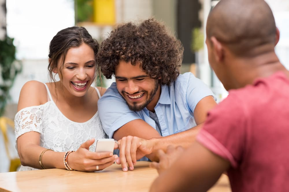 Group of people laughing while looking at a smart phone