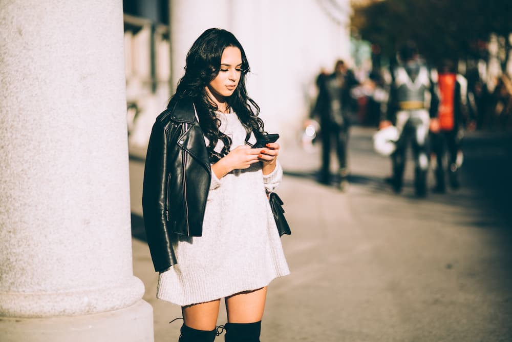 Woman standing on street corner browsing her cell phone