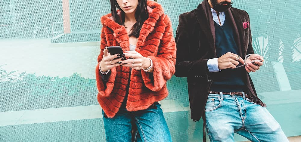 Woman and man standing outside browsing their cell phones